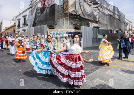 pretty Mexican indigenous women wearing brightly colored traditional costumes take part in parade in historic center - Stock Photo