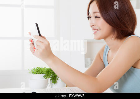 Young woman holding mobile phone with smile, - Stock Photo