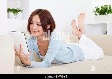 Young woman lying on sofa and using note pad with smile, - Stock Photo