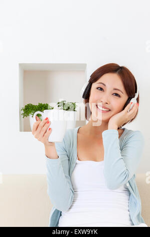 Young woman holding coffee cup and wearing headphone, - Stock Photo
