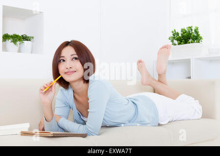 Young woman lying down on front and holding a pencil with smile, - Stock Photo
