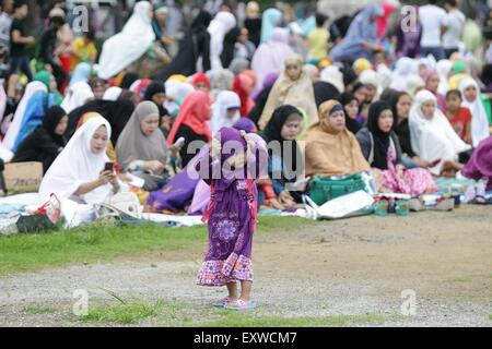 Manila, Philippines. 17th July, 2015. A young Muslim girl holds on to her hijab at the Quirino Grandstand in Manila - Stock Photo
