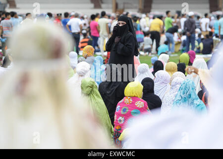 Manila, Philippines. 17th July, 2015. A Filipino Muslim uses her mobile phone at the Quirino Grandstand in Manila - Stock Photo
