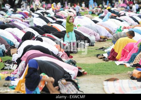 Manila, Philippines. 17th July, 2015. A young girl observes Muslims during their morning prayer at the Quirino Grandstand - Stock Photo