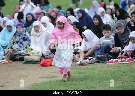 Manila, Philippines. 17th July, 2015. A young Muslim girl plays in the park at the Quirino Grandstand in Manila - Stock Photo