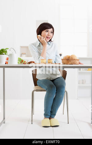 Young woman holding a bread and looking away with smile, - Stock Photo