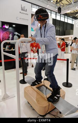 Shanghai, China. 17th July, 2015. A visitor experiences a skiing machine which is based on the 5G mobile communication - Stock Photo