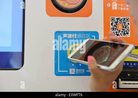 Shanghai, China. 17th July, 2015. A visitor experiences the sound wave payment function of mobile phone during the - Stock Photo