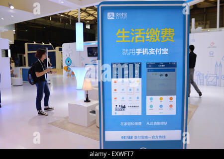 Shanghai, China. 17th July, 2015. A visitor watches mobile payment app during the Mobile World Congress Shanghai - Stock Photo