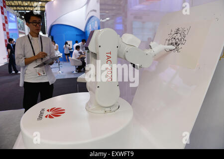 Shanghai, China. 17th July, 2015. A robert painter paints pictures in the orders of controller during the Mobile - Stock Photo