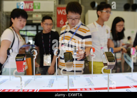 Shanghai, China. 17th July, 2015. People watch smart hand rings during the Mobile World Congress Shanghai in Shanghai, - Stock Photo