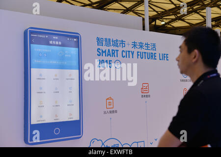 Shanghai, China. 17th July, 2015. A visitor watches the introduction for mobile payment app during the Mobile World - Stock Photo