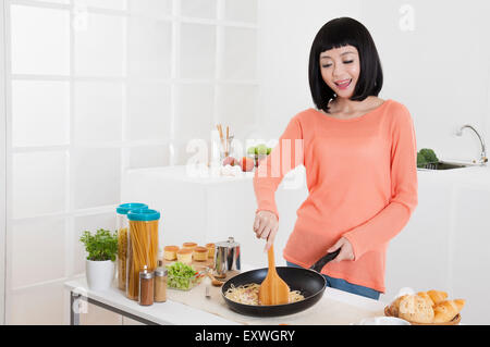 Young woman cooking in the kitchen with smile, - Stock Photo