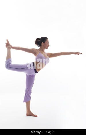 Woman practicing yoga and standing with one leg, - Stock Photo