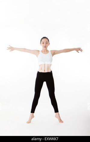 Woman practicing yoga with arms outstretched, - Stock Photo