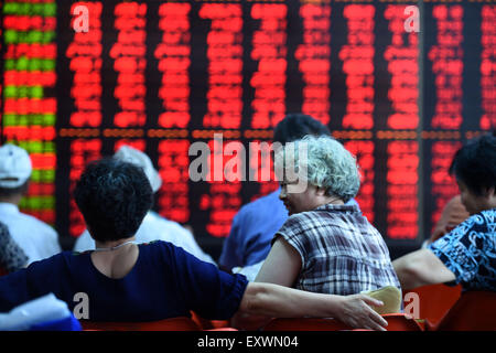 Shenyang, China. 17th July, 2015. Investors look through stock information at a trading hall in a securities firm - Stock Photo