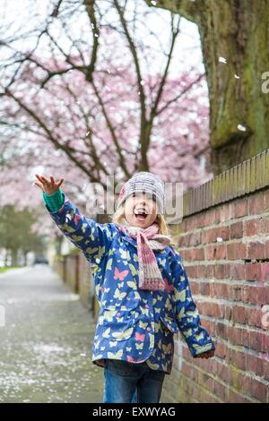 Girl is happy about cherry blossoms, Kiel, Schleswig-Holstein, Germany, Europe - Stock Photo