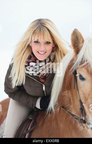 Young woman riding Haflinger horse - Stock Photo