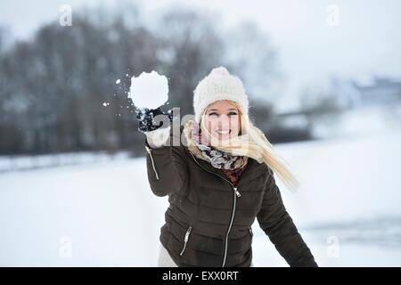 Happy young woman throwing a snowball - Stock Photo