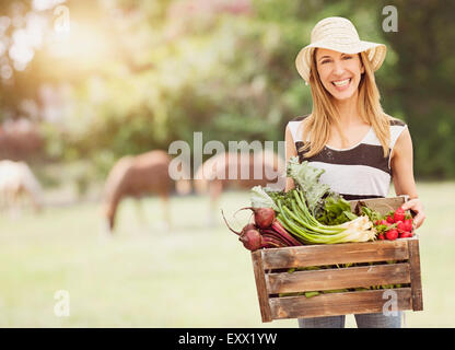Woman carrying fresh vegetables in box - Stock Photo