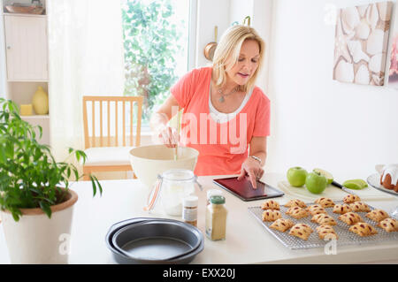 Mature woman baking in kitchen - Stock Photo