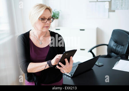 Businesswoman using tablet in office - Stock Photo