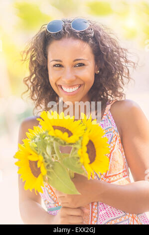 Portrait of smiling woman with sunflowers - Stock Photo