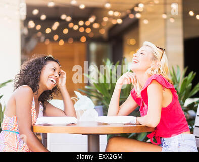 Female friends laughing in street cafe - Stock Photo