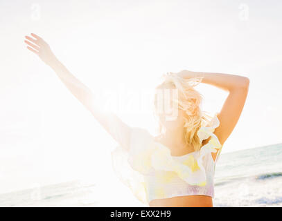 Young woman smiling on beach - Stock Photo