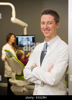 Portrait of dentist with colleague and patient (8-9) in background - Stock Photo