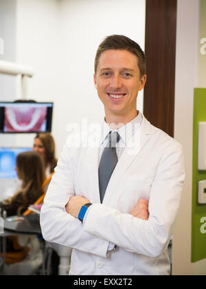 Portrait of dentist with colleague and patient in background - Stock Photo