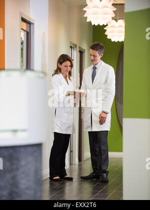 Dentists talking in corridor - Stock Photo