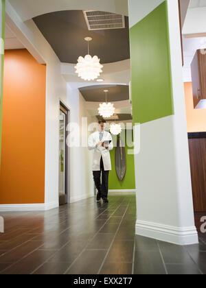 Dentist walking in corridor - Stock Photo