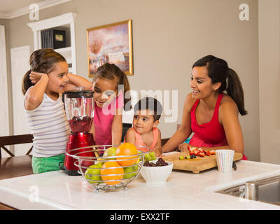Mother and children (2-3, 6-7, 8-9) preparing fruit cocktails - Stock Photo