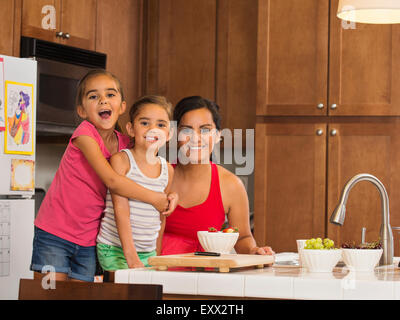 Mother and children (6-7, 8-9) preparing food in kitchen - Stock Photo
