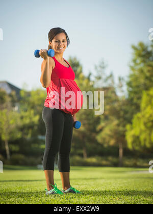 Pregnant woman exercising outdoors - Stock Photo