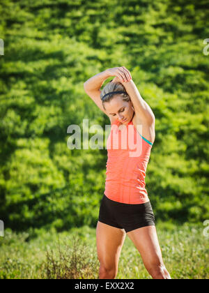 Woman exercising in field - Stock Photo