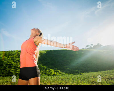 Woman with outstretched arms in field - Stock Photo