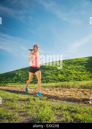 Woman running in field - Stock Photo