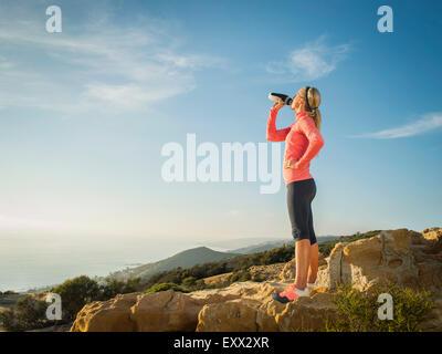 Woman in sportswear drinking water - Stock Photo