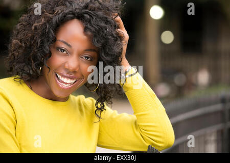 Smiling woman with hand in hair - Stock Photo