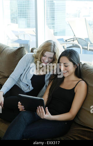 Female friends watching tablet - Stock Photo
