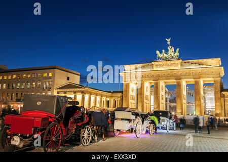 Horse carts in front of illuminated Brandenburg Gate - Stock Photo