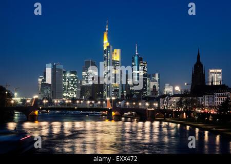 Illuminated riverfront skyline - Stock Photo