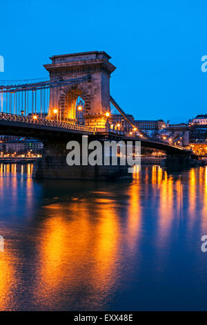Illuminated Chain Bridge and reflections on water - Stock Photo