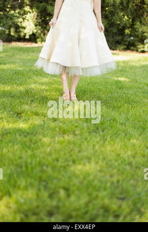 Woman in white dress standing on lawn - Stock Photo
