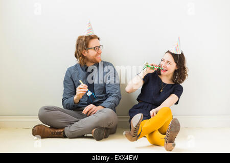 Couple with party horn blowers and party hats sitting on floor - Stock Photo