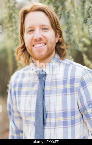 Portrait of smiling man wearing plaid shirt - Stock Photo