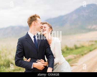 Smiling newlywed couple embracing - Stock Photo