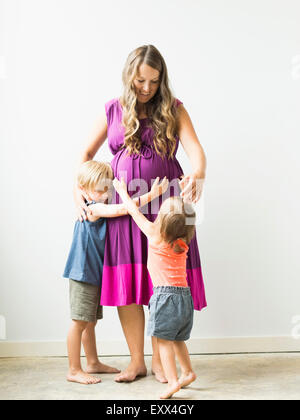 Children (2-3) hugging pregnant mother - Stock Photo
